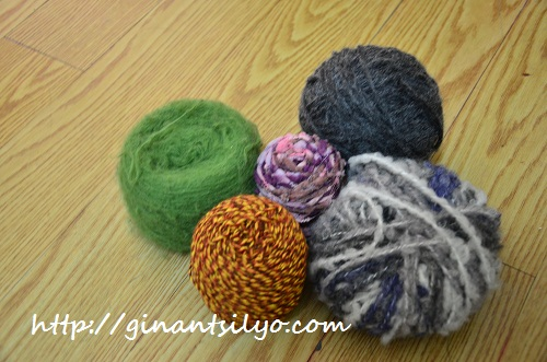 Five balls of yarns of varying texture and color